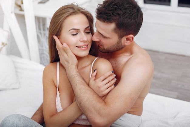 Casal deitado em uma cama em um quarto Foto gratuita