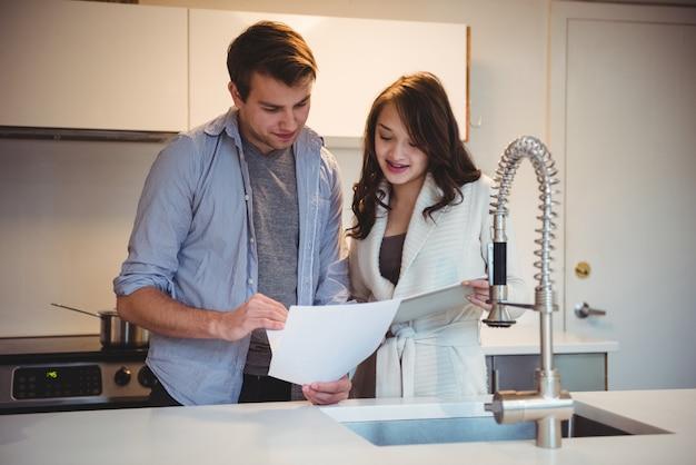 Casal discutindo sobre tablet digital na cozinha Foto gratuita