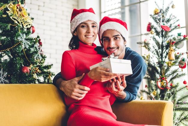 Casal doce romântico em chapéus de papai noel se divertindo decorando a árvore de natal e sorrindo enquanto comemorava a véspera de ano novo e aproveitando o tempo juntos Foto Premium
