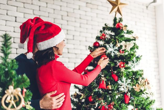 Casal doce romântico em gorros se divertindo decorando a árvore de natal e sorrindo enquanto comemorava a véspera de ano novo Foto Premium