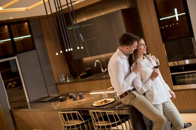 Casal doce tomando vinho tinto depois de um jantar romântico na cozinha de luxo Foto Premium
