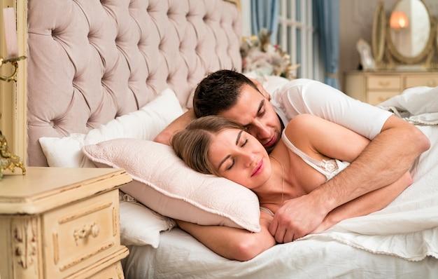 Casal dormindo na cama abraçada Foto gratuita