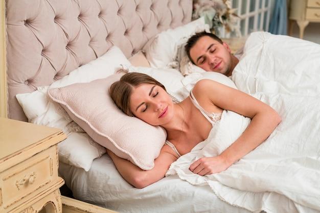 Casal dormindo na cama com edredom Foto gratuita