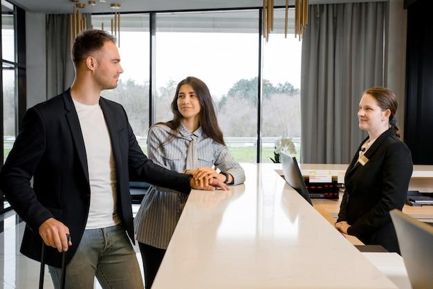 Casal e recepcionista no balcão do hotel. jovem casal em viagem de negócios fazendo check-in no hotel Foto Premium