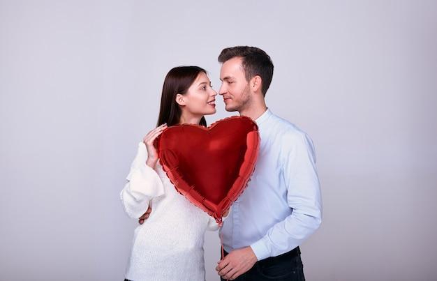 Casal elegante em um fundo cinza com um coração vermelho. Foto Premium