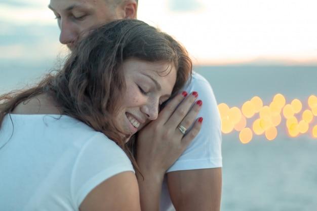 Casal em abraços românticos de amor no deserto de areia. noite, atmosfera romântica, na areia queimar velas Foto Premium