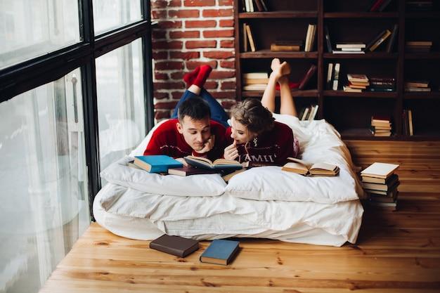 Casal em camisolas vermelhas de natal lendo livros no colchão em casa Foto Premium