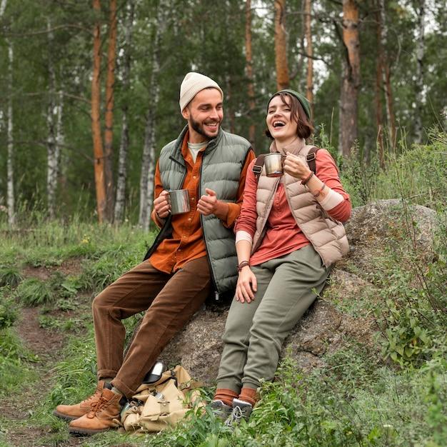 Casal em foto completa curtindo uma bebida quente na natureza Foto gratuita