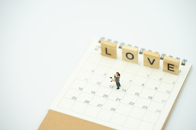 Casal em miniatura 2 pessoas em pé no calendário. dia 14 encontra o dia dos namorados Foto Premium