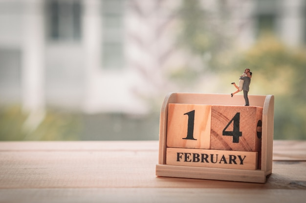 Casal em miniatura com calendário de madeira. 14 de fevereiro. dia dos namorados. Foto Premium