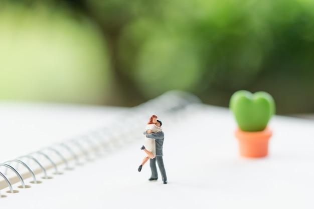 Casal em miniatura pessoas em pé no livro. Foto Premium
