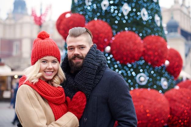 Casal em pé ao lado da árvore de natal Foto gratuita