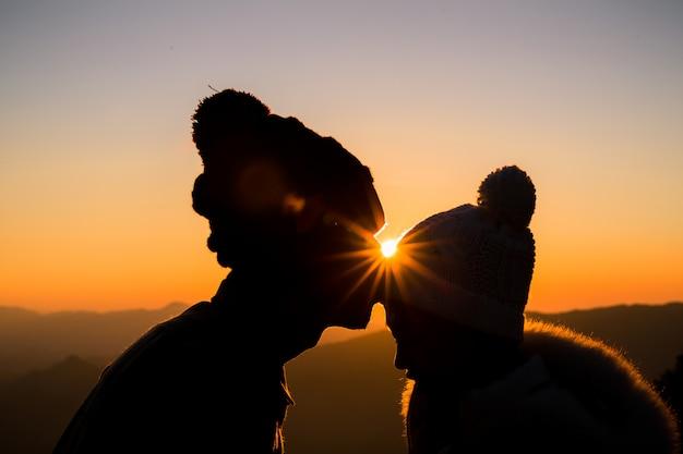 Casal em silhueta de luz de fundo de amor na colina no tempo do sol Foto gratuita
