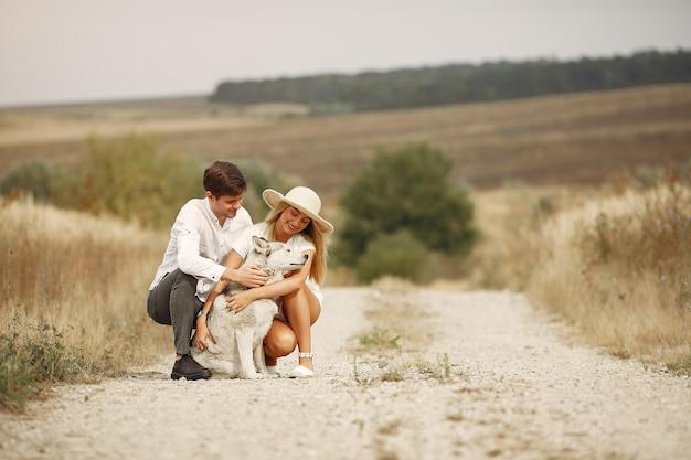 Casal em um campo de outono brincando com um cachorro Foto gratuita