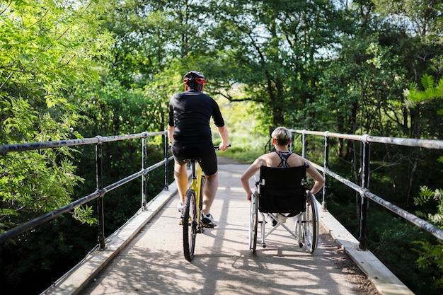 Casal em um exercício juntos em uma bicicleta e em uma cadeira de rodas Foto Premium