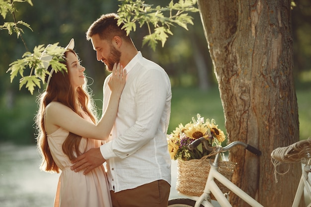 Casal em um parque de verão. pessoas com bicicletas vintage. menina com um chapéu. Foto gratuita