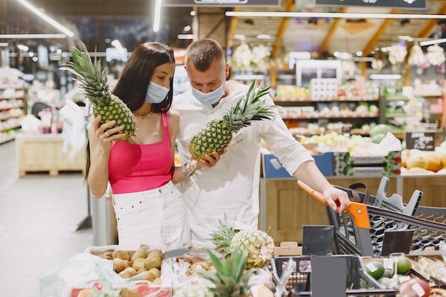Casal em um supermercado. senhora com uma máscara médica. as pessoas compram. Foto gratuita