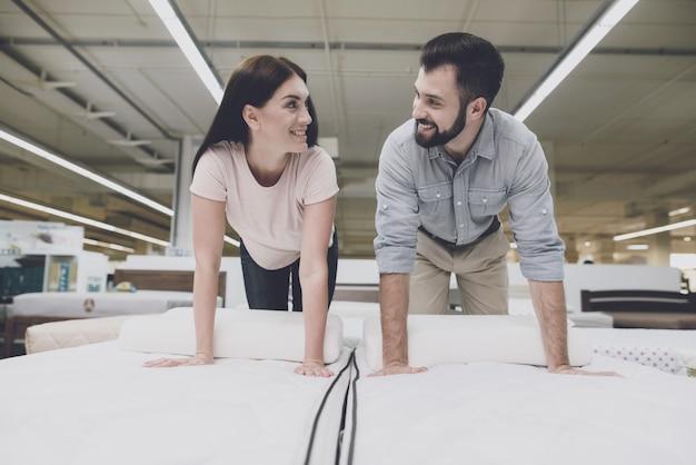 Casal em uma grande loja inspeciona o colchão antes de comprar. Foto Premium