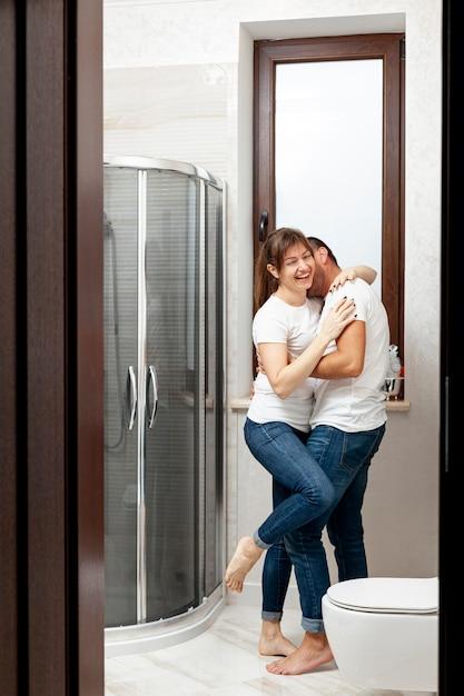 Casal engraçado beijando no banheiro Foto gratuita