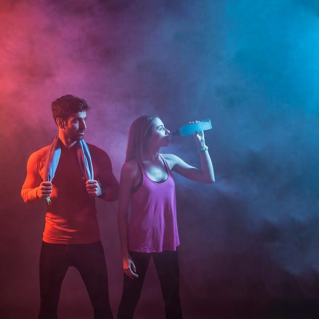 Casal esportivo em estúdio escuro Foto gratuita