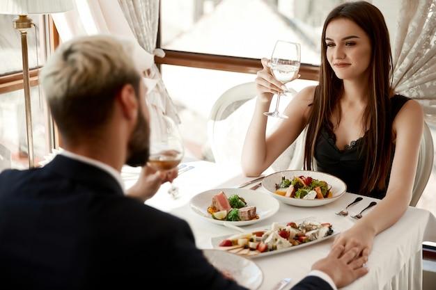 Casal está bebendo vinho branco no jantar romântico no restaurante e de mãos dadas Foto gratuita