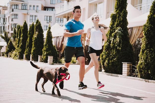 Casal está correndo na estrada com cachorro grande Foto Premium