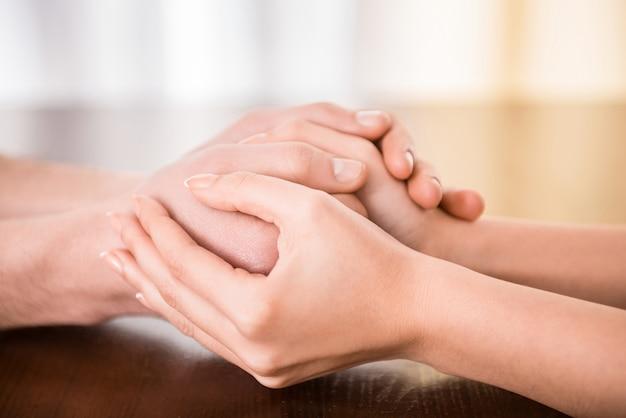 Casal está de mãos dadas em cima da mesa. Foto Premium