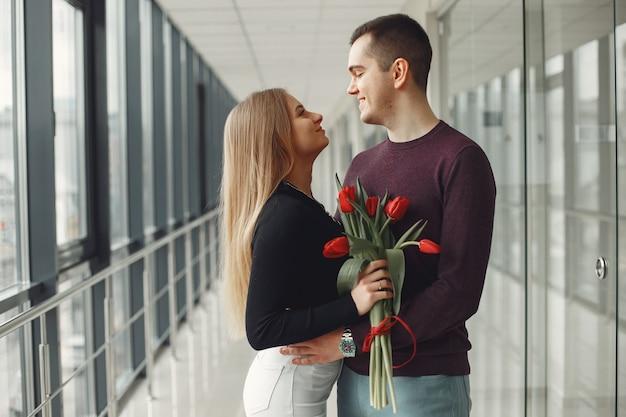 Casal europeu está de pé em um salão com um monte de tulipas vermelhas Foto gratuita