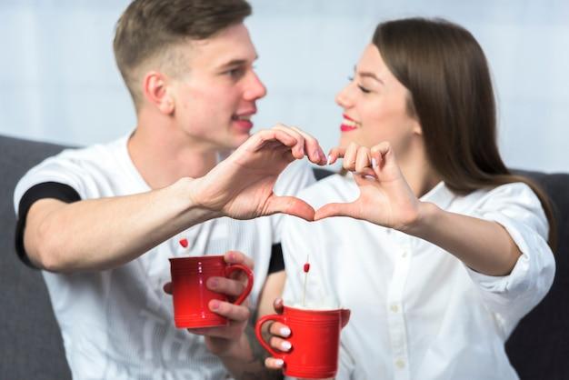 Casal fazendo formato de coração com as mãos Foto gratuita