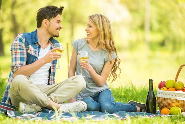 Casal fazendo piquenique no parque e bebendo vinho. Foto Premium