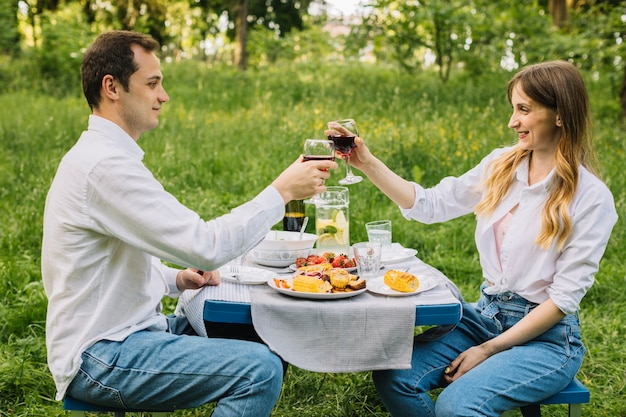 Casal fazendo um piquenique romântico na natureza Foto gratuita