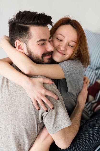 Casal feliz abraçando dentro de casa Foto gratuita