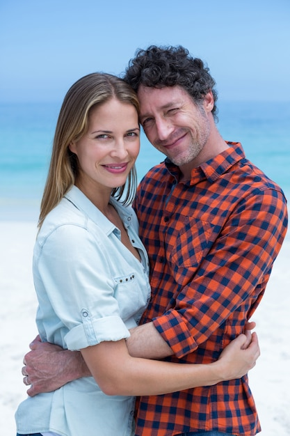 Casal feliz abraçando na praia Foto Premium