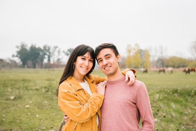 Casal feliz abraçando no prado Foto gratuita