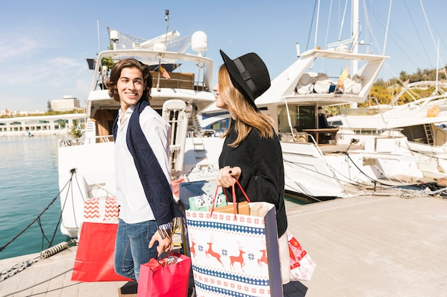 Casal feliz andando com sacolas de compras Foto gratuita