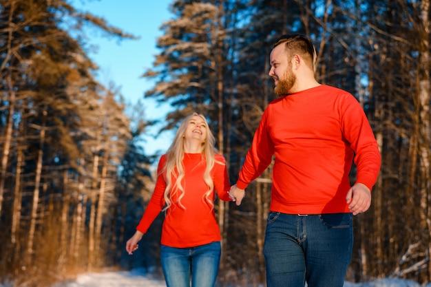 Casal feliz andando na floresta de neve Foto Premium