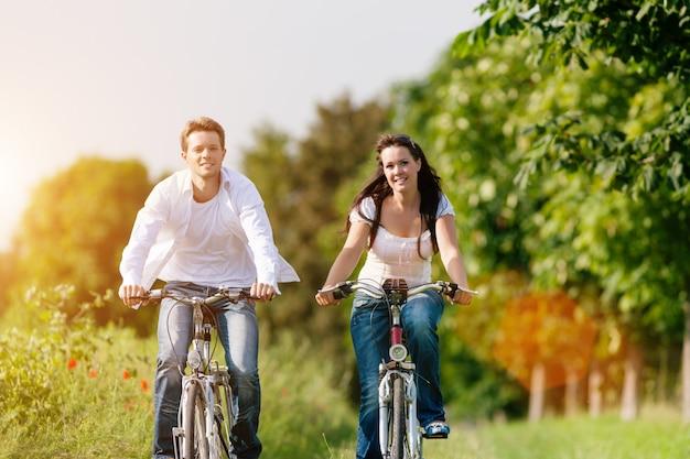 Casal feliz, andar de bicicleta ao longo de uma estrada ensolarada Foto Premium
