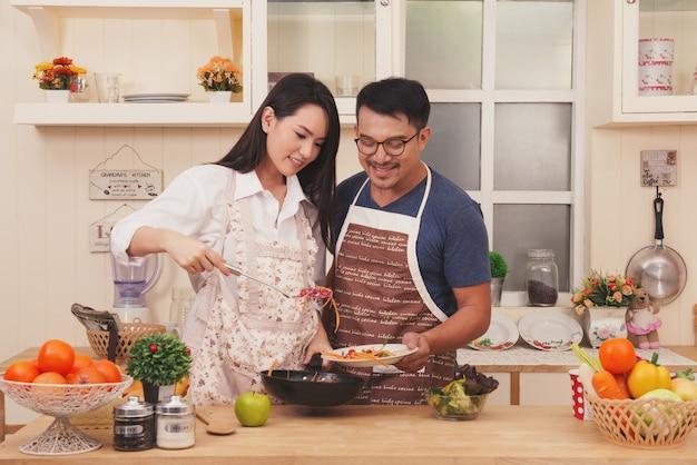 Casal feliz ásia cozinhar comida saudável em sua cozinha loft em casa Foto Premium