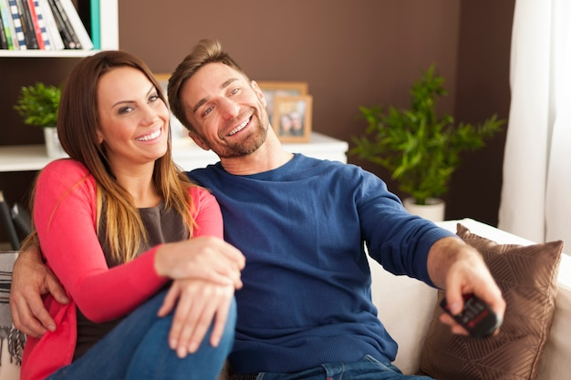 Casal feliz assistindo tv em casa Foto gratuita