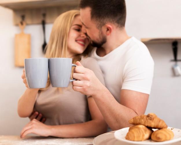 Casal feliz bebendo leite com croissants Foto gratuita
