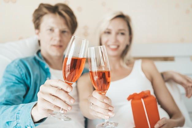 Casal feliz bebendo vinho no quarto Foto gratuita