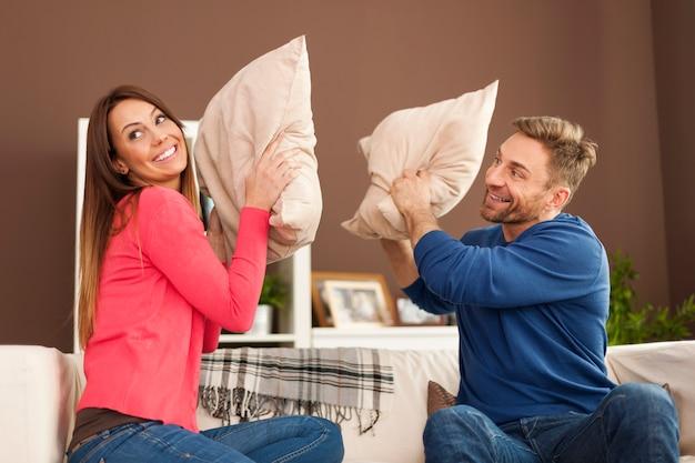 Casal feliz brigando de travesseiro na sala de estar Foto gratuita