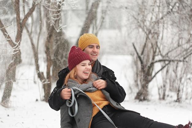Casal feliz brincando ao ar livre na neve Foto gratuita