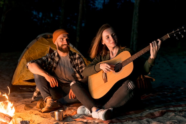Casal feliz cantando e tocando violão Foto gratuita