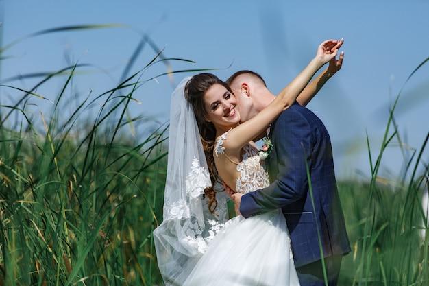 Casal feliz casamento andando na ponte de madeira. emocional noiva e o noivo abraçando suavemente ao ar livre. Foto Premium