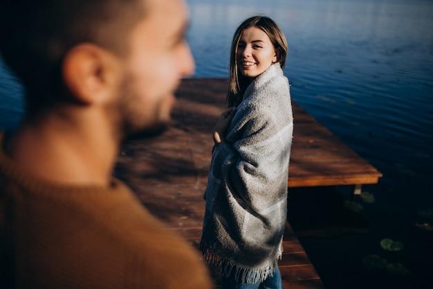 Casal feliz com cobertor pelo rio Foto gratuita