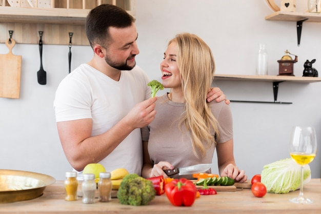 Casal feliz comendo brócolis Foto gratuita