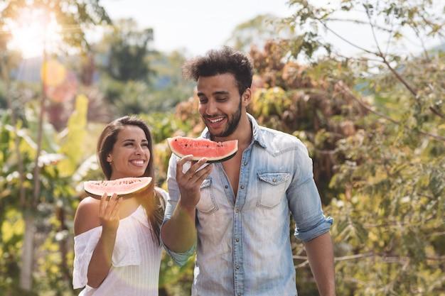Casal feliz comendo melancia juntos alegre Foto Premium