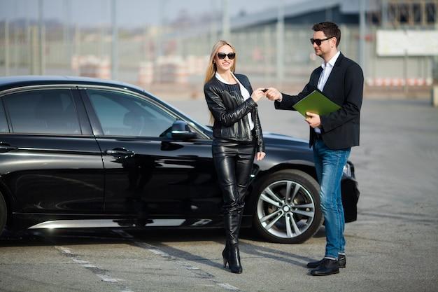 Casal feliz compra novo carro preto moderno Foto Premium