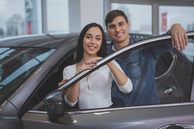 Casal feliz comprando carro novo no salão da concessionária Foto Premium